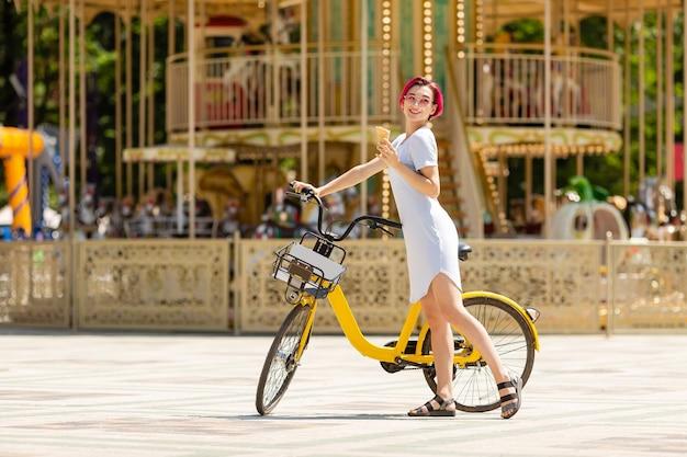 Jonge vrouw met roze haren loopt in het park met een fiets die ijs eet in de zomer.