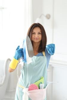 Jonge vrouw met rubberen handschoenen, klaar om schoon te maken en te strijken