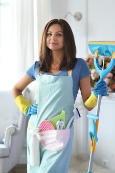 Jonge vrouw met rubberen handschoenen, klaar om schoon te maken