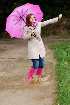 Jonge vrouw met rubberen laarzen veel plezier in regenachtige dag