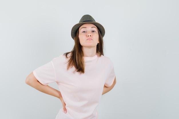 Jonge vrouw met rugpijn in roze t-shirt, hoed en uitgeput op zoek, vooraanzicht.