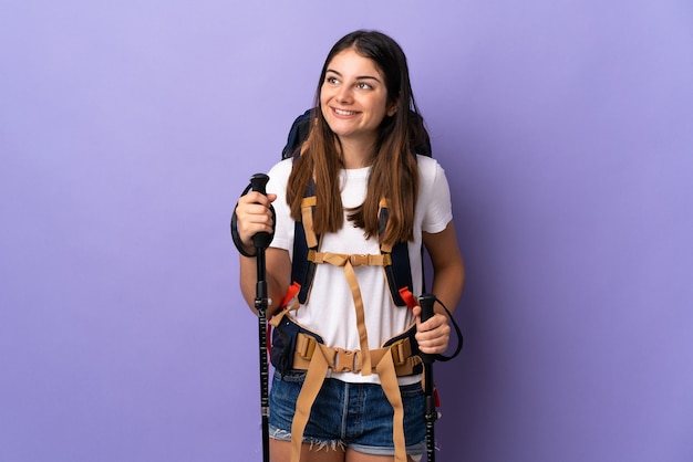 Jonge vrouw met rugzak en trekkingstokken die op purpere muur worden geïsoleerd die een idee denken terwijl het opzoeken