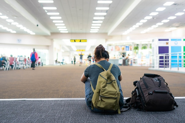 Jonge vrouw met rugzak in luchthaven dichtbij vluchttijdschema