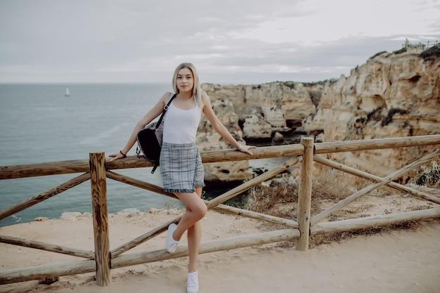 Jonge vrouw met rugzakreiziger op de horizon van het achtergrondstrandzeegezicht.