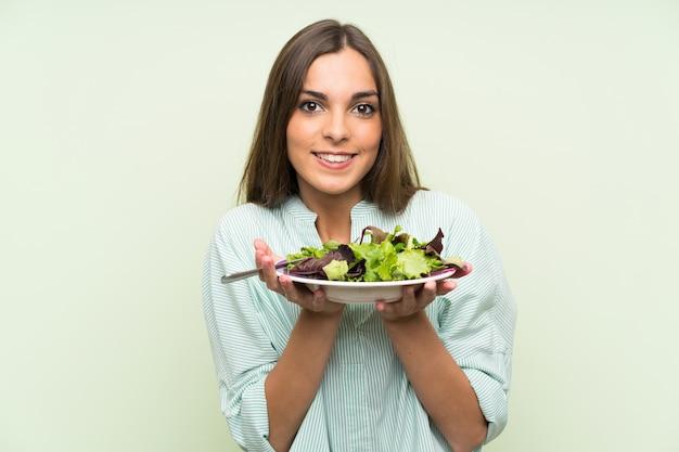 Jonge vrouw met salade over geïsoleerde groene muur