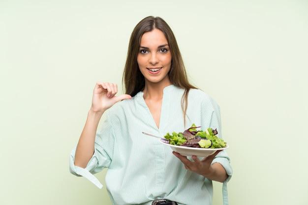 Jonge vrouw met salade over geïsoleerde groene trots en zelf-tevreden muur