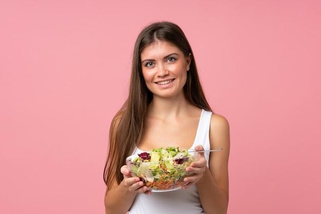 Jonge vrouw met salade over geïsoleerde roze muur