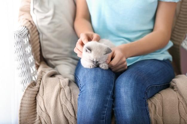 Jonge vrouw met schattig klein katje thuis