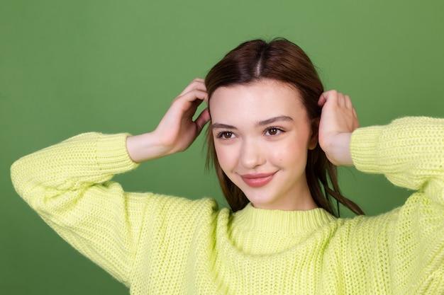 Jonge vrouw met schone, perfecte natuurlijke huid en make-up, bruine grote lippen op groene muur, gelukkig positief, vrolijk lachend poserend bewegend