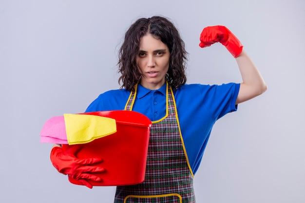 Jonge vrouw met schort en rubberen handschoenen met emmer met schoonmaakgereedschap vuist opheffen met biceps op zoek zelfverzekerd klaar om schoon te maken staande over geïsoleerde witte achtergrond