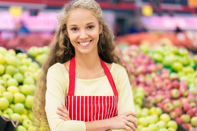 Jonge vrouw met schort in supermarkt