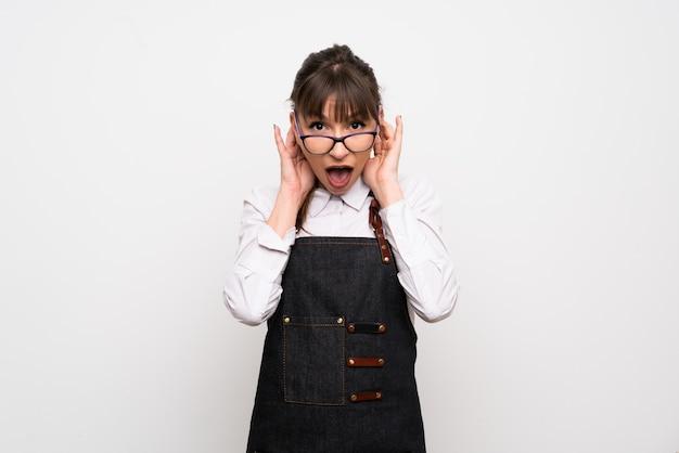 Jonge vrouw met schort met een bril en verrast