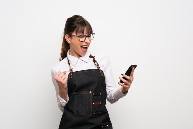 Jonge vrouw met schort met telefoon in overwinningspositie