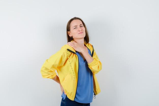 Jonge vrouw met schouderpijn in t-shirt en ziet er moe uit, vooraanzicht.