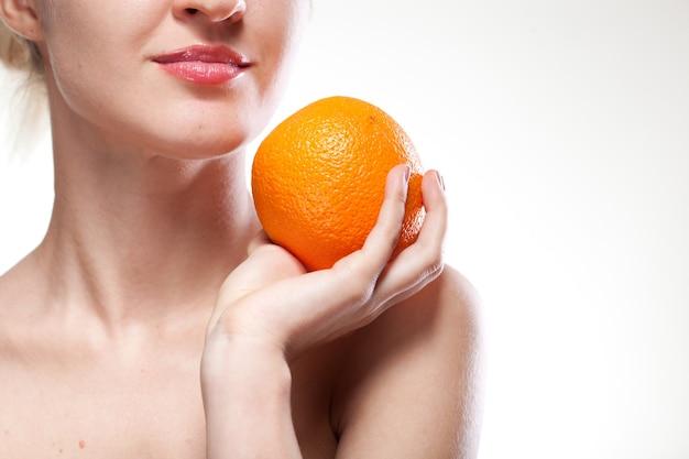 Jonge vrouw met sinaasappel die op wit wordt geïsoleerd