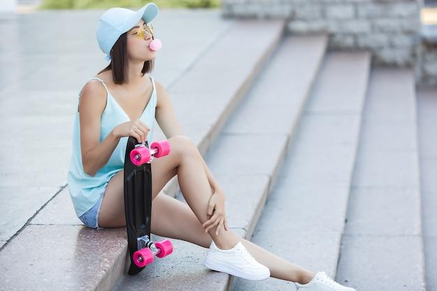 Jonge vrouw met skate. vrouwelijke skater. mooie vrouw buitenshuis.