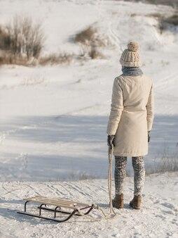 Jonge vrouw met slee gekleed in casual mooie trendy winterkleren genieten van wintersport