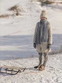 Jonge vrouw met slee gekleed in casual mooie trendy winterkleren genieten van wintersportspellen