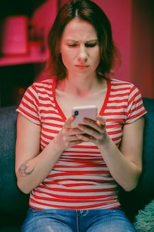 Jonge vrouw met slimme telefoon kijken naar mobiel scherm met behulp van mobiele apps om te winkelen