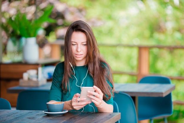 Jonge vrouw met slimme telefoon terwijl het zitten alleen in koffiewinkel tijdens vrije tijd
