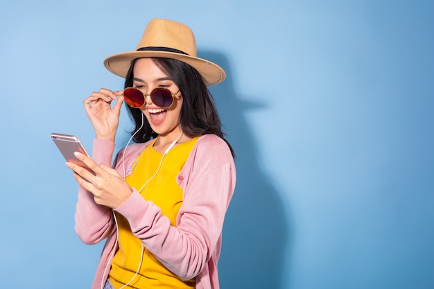 Jonge vrouw met smartphone en oortelefoons