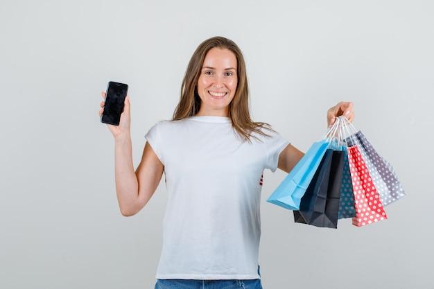Jonge vrouw met smartphone en papieren zakken in wit t-shirt, korte broek en op zoek vrolijk
