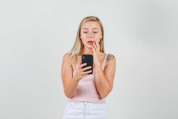 Jonge vrouw met smartphone in hemd, minirok en verbaasd kijken.