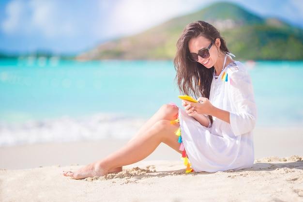 Jonge vrouw met smartphone tijdens tropische strandvakantie.