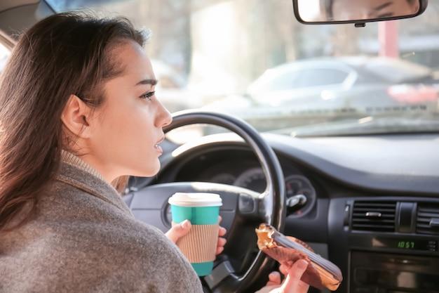 Jonge vrouw met snack in auto tijdens verkeersopstopping