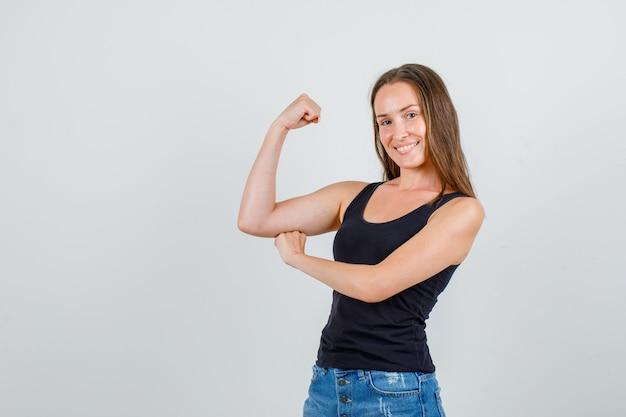 Jonge vrouw met spier van arm in hemd, korte broek en sterk op zoek. vooraanzicht.