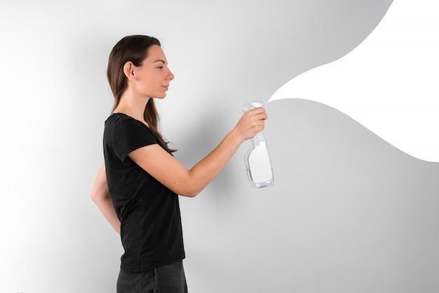 Jonge vrouw met spray plastic fles met schoonmaak vloeistof. lente schoonmaak concept. desinfecteren