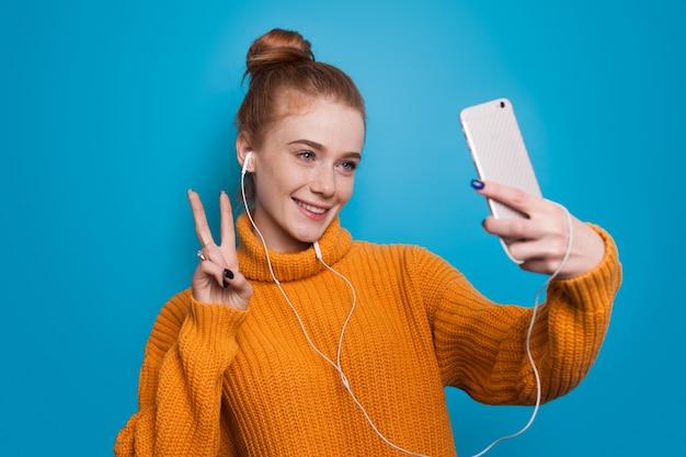 Jonge vrouw met sproeten en rood haar begroet iemand op haar telefoon terwijl ze een koptelefoon draagt op een blauwe studiomuur