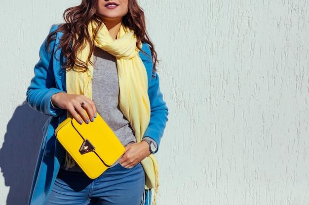 Jonge vrouw met stijlvolle gele handtas en trendy blauwe jas dragen. lente vrouwelijke kleding en accessoires. mode. kleur van 2021