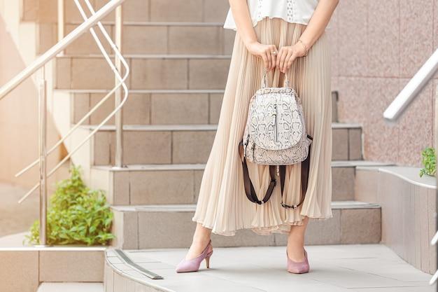 Jonge vrouw met stijlvolle tas in de buurt van winkel buitenshuis