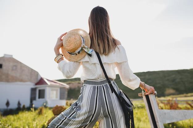 Jonge vrouw met strohoed op het platteland