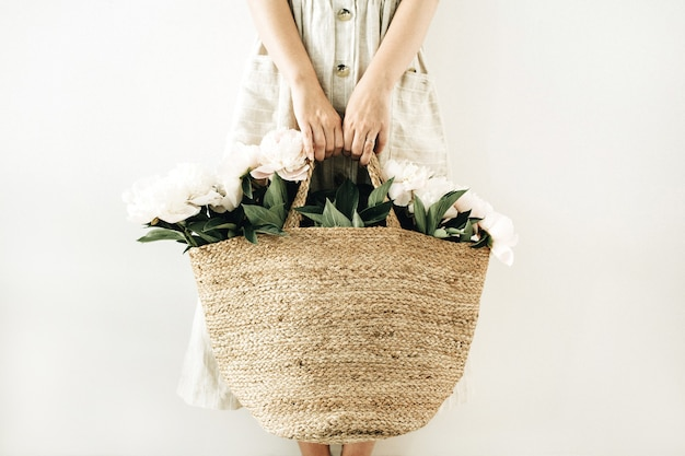 Jonge vrouw met strozak met witte pioenroos bloemen op wit oppervlak Premium Foto