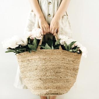Jonge vrouw met strozak met witte pioenroos bloemen op wit oppervlak