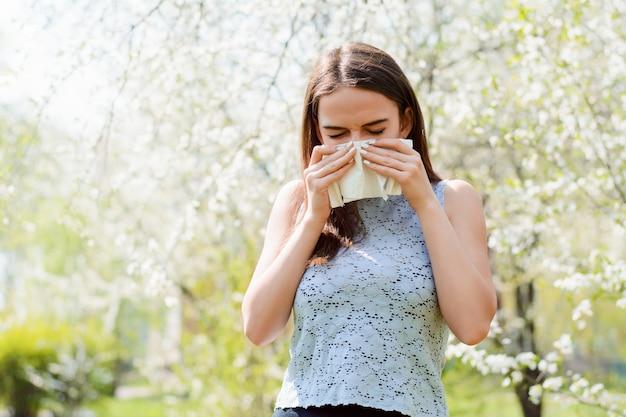 Jonge vrouw met symptomen van coronavirus niezen staande in bloeiende boomgaard. jonge zieke die griep heeft, lopende neus en koorts heeft die zich in de lentepark bevindt