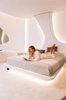 Jonge vrouw met tablet in het bed op de luxe appartement