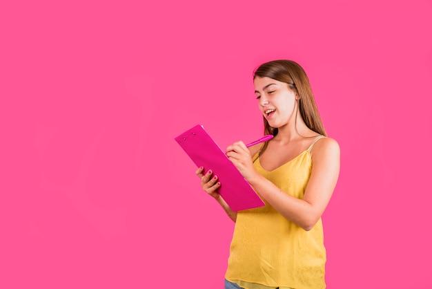 Jonge vrouw met tablet voor papier op roze achtergrond