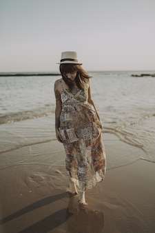Jonge vrouw met tatoeages die een jurk en een strohoed draagt op de wazige oceaan