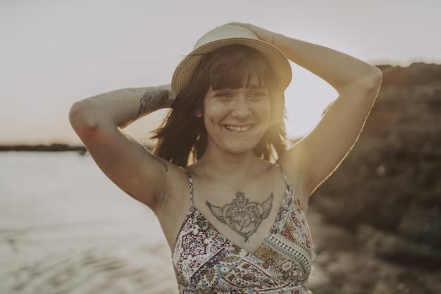 Jonge vrouw met tatoeages met een jurk en strohoed op een wazige oceaanachtergrond
