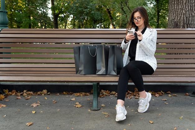 Jonge vrouw met telefoon en boodschappentassen in park. online winkelen. kortingen, promoties, zwarte vrijdag.