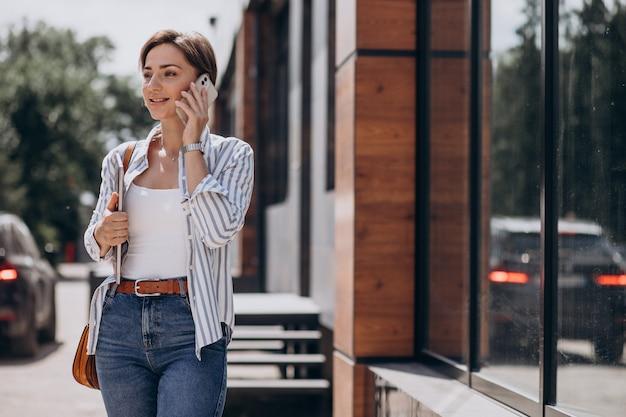 Jonge vrouw met telefoon en computer die buiten de straat loopt