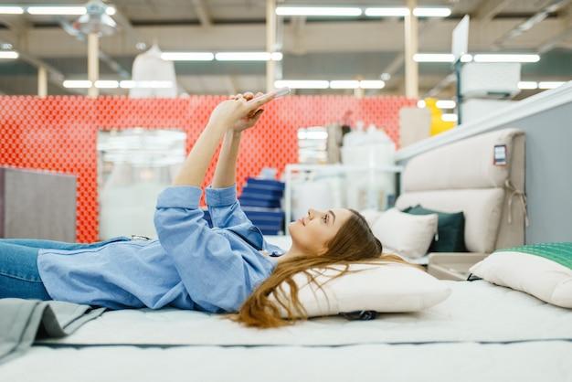 Jonge vrouw met telefoon liggend in bed in de showroom van de meubelwinkel.
