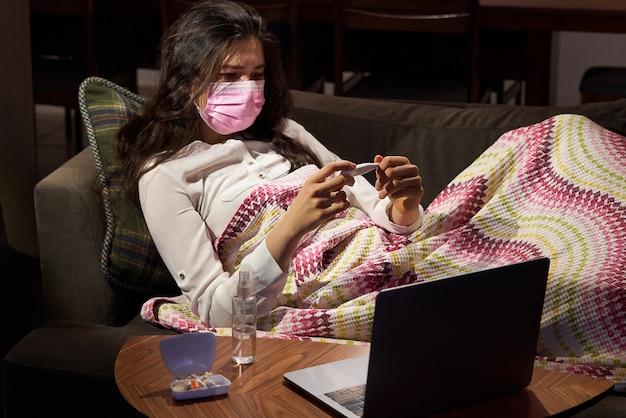 Jonge vrouw met thermometer op sofa kreeg koorts, gevangen, ziek meisje met griep symptomen, griep of virus concept