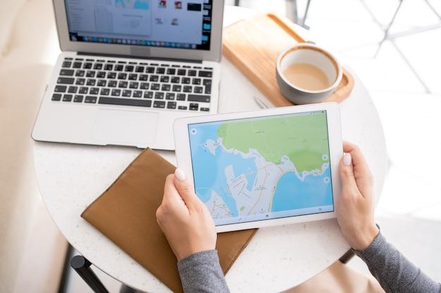 Jonge vrouw met touchpad met kaart op het display zittend aan tafel, cappuccino hebben en gadgets gebruiken