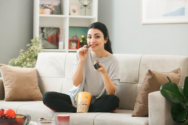 Jonge vrouw met tv-afstandsbediening eet koekje zittend op de bank achter de salontafel in de woonkamer