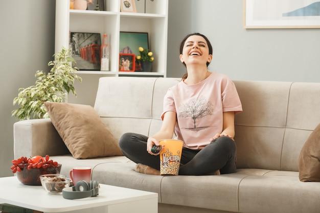 Jonge vrouw met tv-afstandsbediening zittend op de bank achter de salontafel in de woonkamer
