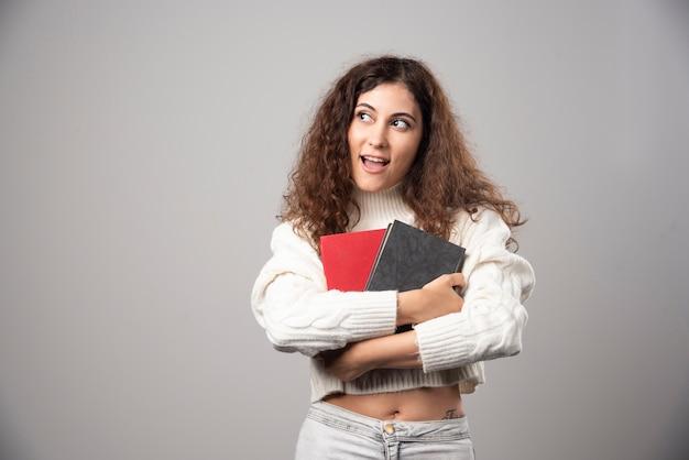Jonge vrouw met twee boeken op een grijze muur. hoge kwaliteit foto